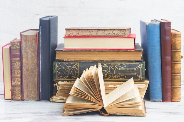 Zestaw starych książek na białym drewnianym