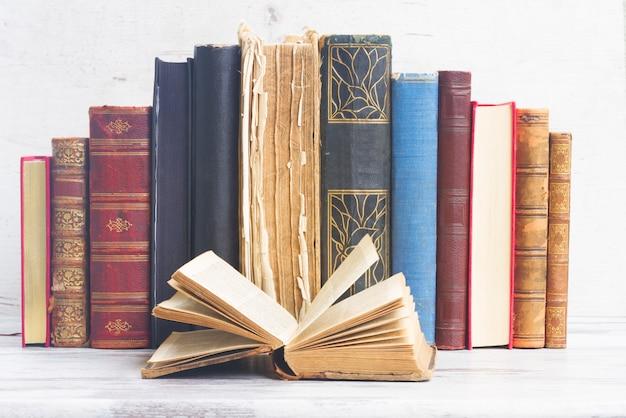 Zestaw starych książek z otwartą na białym drewnianym