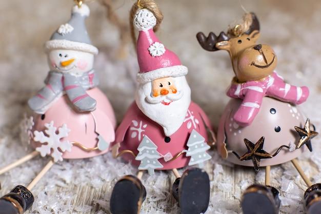 Zestaw statuetek świętego mikołaja, bałwana i jelenia świąteczny wystrój, ciepłe światła bokeh.