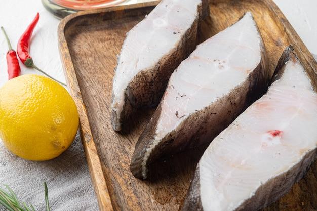 Zestaw stek z surowej ryby, ze składnikami i ziołami rozmarynowymi, na białym tle kamiennego stołu