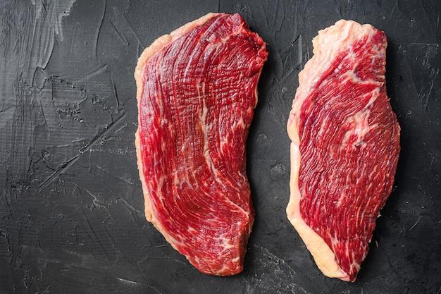 Zestaw steków surowej wołowiny picanha na czarnym tle z teksturą, widok z góry miejsca na tekst.