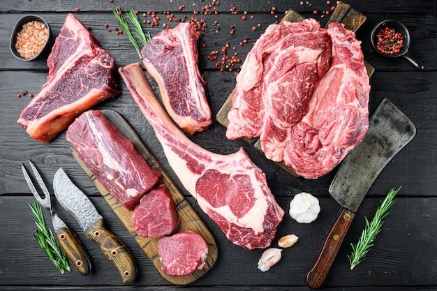 Zestaw steków z surowego mięsa wołowego, tomahawk, t bone, stek klubowy, żeberka i kawałki polędwicy, na czarnym drewnianym stole, widok z góry na płasko