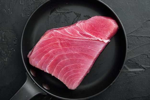 Zestaw steków z surowego tuńczyka, na patelni żeliwnej, na czarnym kamieniu