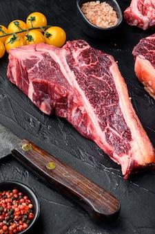 Zestaw steków z wołowiny włoskiej po florencku t z kością, na stole z czarnego kamienia