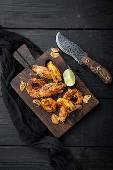 Zestaw sticky mango krewetki lub krewetki, na drewnianej desce, na czarnym drewnianym stole