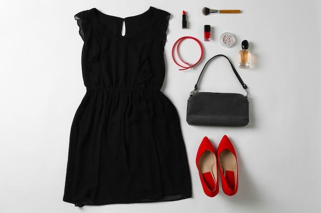 Zestaw stylowych ubrań i akcesoriów dla kobiety na białym tle