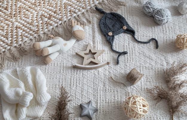 Zestaw stylowych ubranek dziecięcych ręcznie robionych na drutach z różnymi dodatkami w stylu boho, widok z góry.