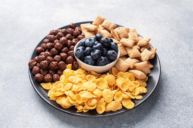 Zestaw suchych płatków zbożowych na śniadanie z mlekiem i jagodami. zdrowa naturalna żywność. kopia przestrzeń szary betonowy stół