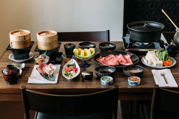 Zestaw sukiyaki zawierający rzadkie plasterki wołowiny wagyu, sos shoyu, japoński melon spadziowy.