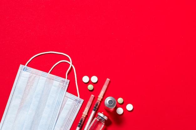 Zestaw suplementów medycznych, takich jak maseczki do twarzy, tabletki, fiolki i strzykawki na czerwonym tle