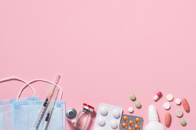 Zestaw suplementów medycznych, takich jak maseczki do twarzy, tabletki, fiolki i strzykawki na różowym tle