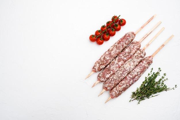 Zestaw surowego mielonego szaszłyka jagnięcego szaszłyk z kebabem, ze składnikami grilla, na białym tle kamiennego stołu, widok z góry płasko leżący, z kopią miejsca na tekst