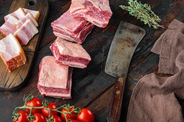 Zestaw surowego mięsa cielęcego cielęcego z krótkim żebrem, ze składnikami i starym nożem tasakowym, na starym ciemnym drewnianym stole, widok z góry płaski leżał