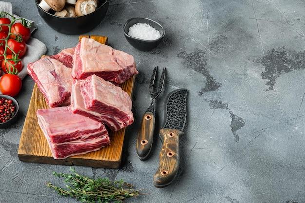 Zestaw surowego mięsa cielęcego z cielęciny, ze składnikami, na szarym kamiennym tle, z miejscem na kopię tekstu