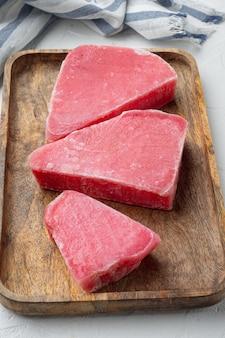 Zestaw surowego mrożonego fileta z tuńczyka, na drewnianej tacy, na białym kamiennym tle