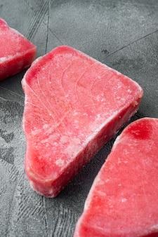 Zestaw surowego mrożonego fileta z tuńczyka, na szarym kamiennym tle