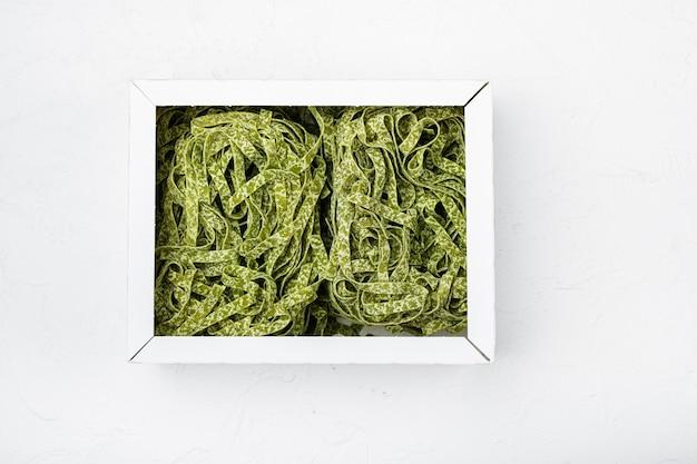Zestaw surowego zielonego makaronu, na białym tle kamiennego stołu, płaski widok z góry