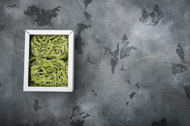 Zestaw surowego zielonego makaronu, na szarym tle kamiennego stołu, płaski widok z góry, z miejscem na kopię tekstu
