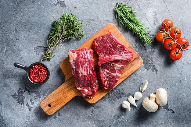 Zestaw surowej wołowiny w alternatywnych kawałkach z innymi składnikami