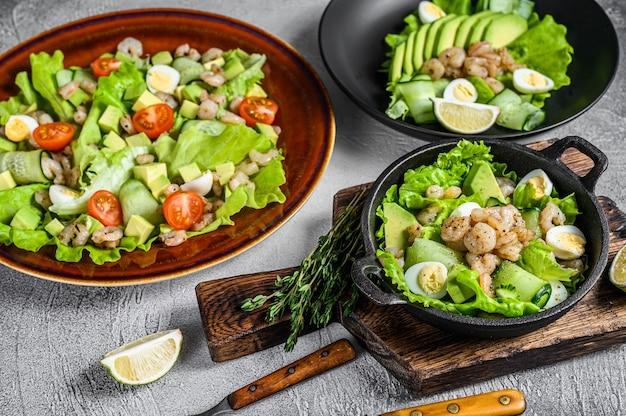 Zestaw surówek z awokado, krewetkami, krewetkami i zieleniną w miseczkach