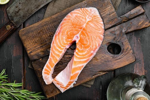 Zestaw surowy stek z łososia, na starym ciemnym tle drewnianego stołu, widok z góry płaski lay