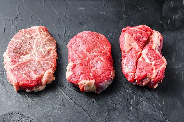 Zestaw surowych alternatywnych kawałków steków wołowych, górnego ostrza, zadu i rolki chuck, na czarnym tle z teksturą, widok z boku.