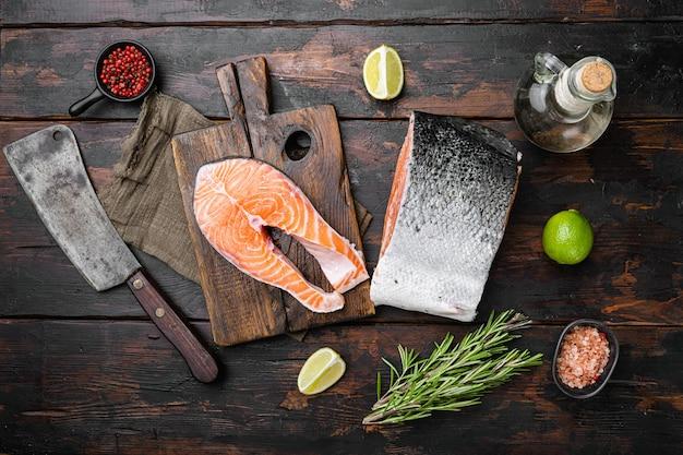 Zestaw surowych ciętych ryb łososia, na starym ciemnym tle drewnianego stołu, widok z góry płaski lay