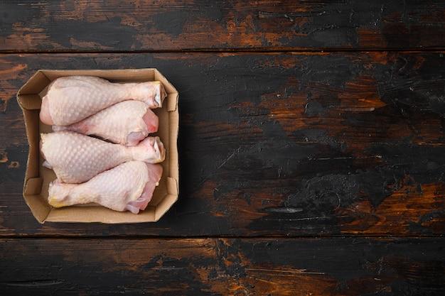 Zestaw surowych i niegotowanych podudzi z kurczaka, w papierowym opakowaniu, na starym ciemnym drewnianym stole, widok z góry na płasko