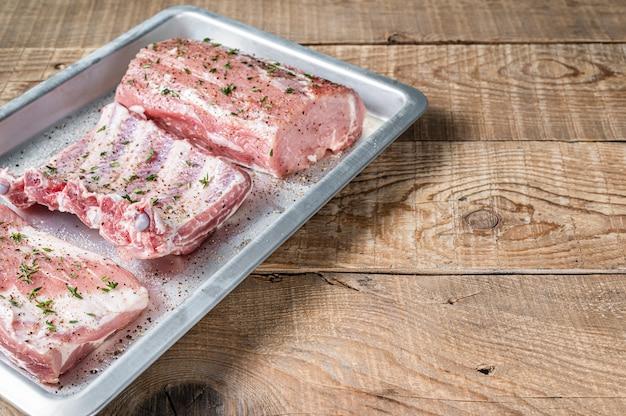 Zestaw surowych kawałków wieprzowiny, schabu, żeberka i mostka.