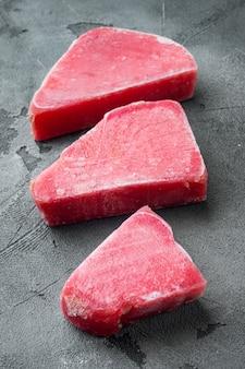Zestaw surowych mrożonych filetów z tuńczyka na szarym kamiennym stole