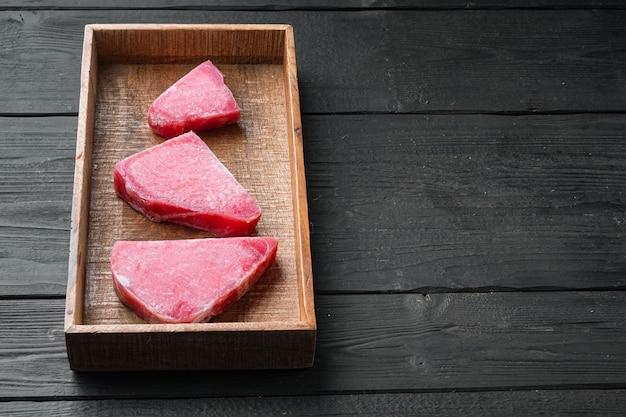 Zestaw surowych mrożonych filetów z tuńczyka, w drewnianym pudełku, na czarnym drewnianym stole
