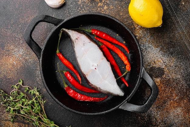 Zestaw surowych ryb, ze składnikami i ziołami rozmarynu, na starym ciemnym rustykalnym tle stołu, widok z góry płaski lay
