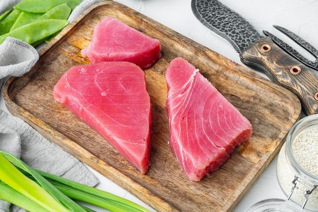 Zestaw surowych składników stek z tuńczyka sezamowego, na drewnianej tacy, na białym kamieniu