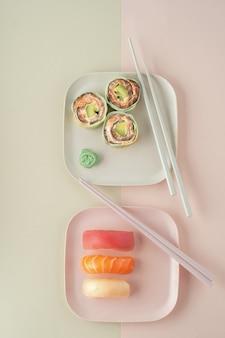 Zestaw sushi, maki i roladki na kolorowych talerzach