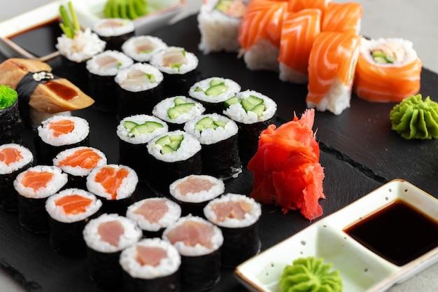 Zestaw sushi maki serwowane na czarnej kamiennej tacy z bliska