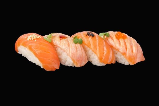 Zestaw sushi nigiri norweski świeży i smażony łosoś, sos sriracha, mikrozielony, sezam, kawior na białym tle