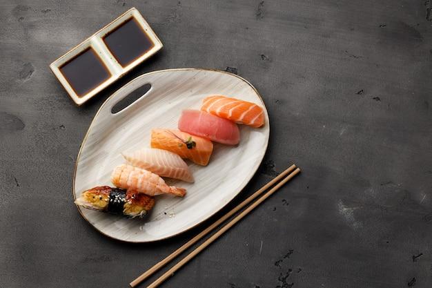Zestaw sushi nigiri podany na talerzu w kolorze ciemnoszarym