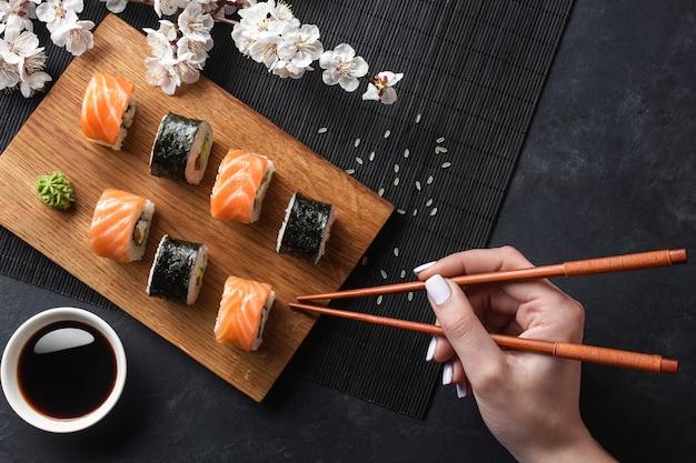 Zestaw sushi, rolki maki, ręka z pałeczkami i gałąź białych kwiatów na kamiennym stole. widok z góry.