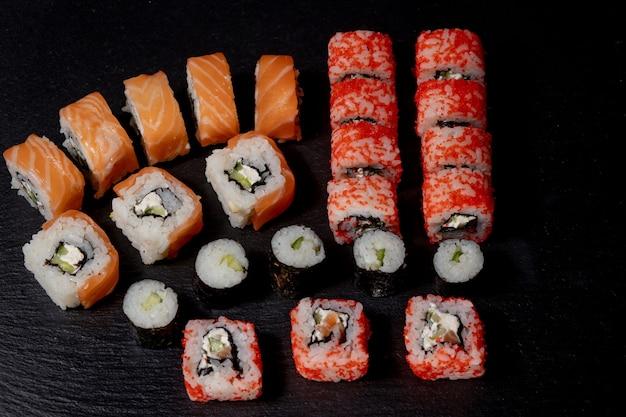 Zestaw sushi roll na czarnym łupku jedzenie ryba filadelfia japoński łosoś pyszne sushi ryż ogórek posiłek tradycyjne wasabi świeże zdrowe smakosz surowy kuchnia