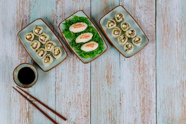 Zestaw sushi roll z sosem sojowym, imbirem i pałeczkami kuchni japońskiej