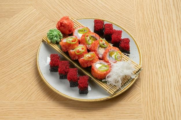 Zestaw sushi składający się z różnych bułeczek z tuńczykiem, łososiem, krewetkami, ikrą tobiko, imbirem, rzodkiewką daikon, czarnym ryżem z mątwą i wiśniami wasabi.