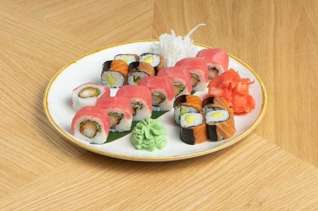 Zestaw sushi składający się z różnych bułeczek z tuńczykiem, łososiem, krewetkami, imbirem, rzodkiewką daikon i wasabi.