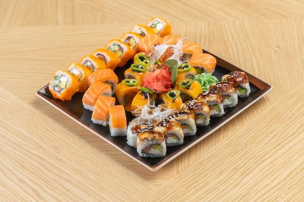 Zestaw sushi składający się z różnych bułeczek z węgorzem, tuńczykiem, łososiem, krewetkami, imbirem, rzodkiewką daikon i wasabi.