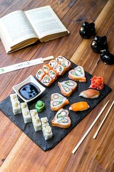 Zestaw sushi z boczkiem, imbirem i sosem sojowym z wasabi na talerzu i książką na stole