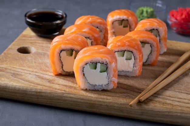 Zestaw sushi z łososiem i serem philadelphia na desce na szarym tle. zdrowe jedzenie. zbliżenie