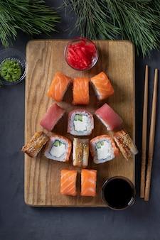 Zestaw sushi z łososiem, tuńczykiem i węgorzem jako choinka podawany na drewnianej desce jako dekoracja świąteczna na ciemnym tle. widok z góry