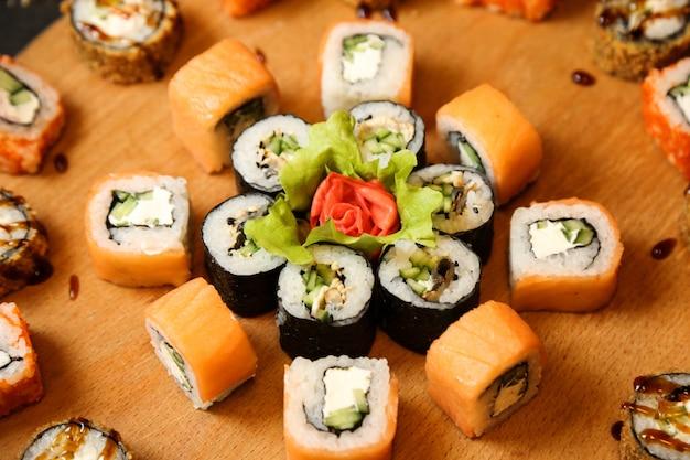 Zestaw sushi z łososiem warzywami twarogiem imbirem wasabi widok z boku