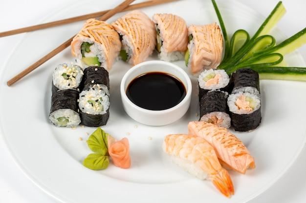 Zestaw sushi z sosem sojowym na środku talerza i pałeczkami