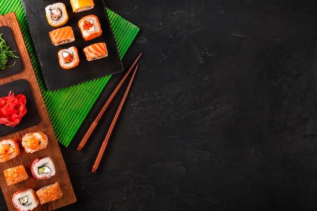 Zestaw sushi z wasabi i imbirem na czarnej kamiennej tacy na czarnym stole. widok z góry