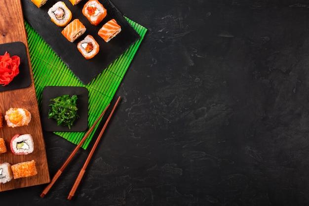 Zestaw sushi z wasabi i imbirem na czarnej kamiennej tacy na czarnym stole.